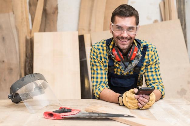 Een mannelijke timmerman die zich achter de werkbank bevindt die mobiele telefoon met behulp van