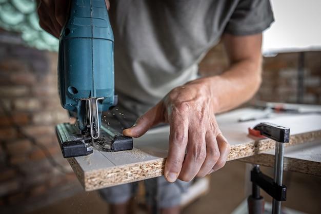 Een mannelijke timmerman snijdt een hout met een elektrische decoupeerzaag, werkend met een boom.