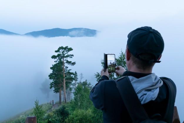 Een mannelijke toerist met een pet maakt foto's van de ochtendmens en zijn reis op zijn mobiele telefoon vroeg in de nacht.