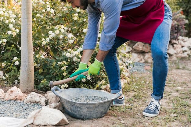 Een mannelijke tuinman die in de tuin werkt