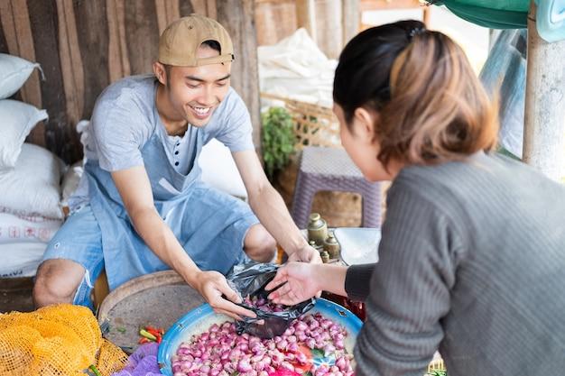 Een mannelijke verkoper met een plastic zak nodigt vrouwelijke kopers uit om sjalotten te selecteren bij de groentetribune