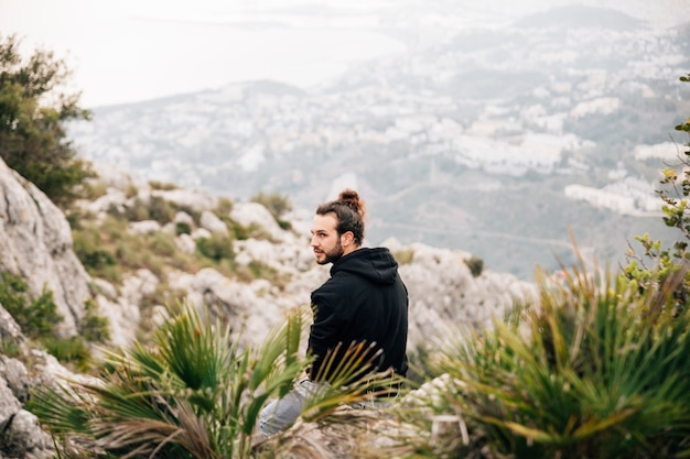 Een mannelijke wandelaarzitting bovenop rotsachtige berg
