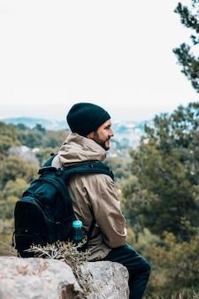 Een mannelijke wandelaarzitting op rots met zijn rugzak die mening bekijkt
