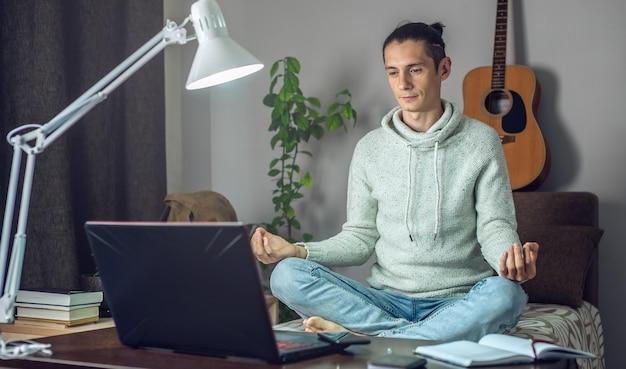 Een mannelijke werknemer mediteert in de lotuspositie terwijl hij thuis met een laptop op afstand hard werkt