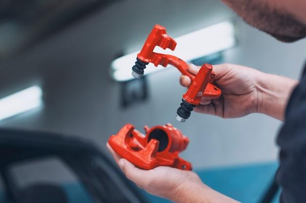 Een mannelijke werktuigkundige monteert een remklauw van een auto. een man houdt auto-onderdelen in zijn handen in een autoservice.