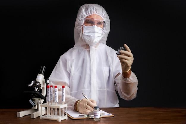 Een mannelijke wetenschapper test met een microscoop een monster van biologische buisjes die besmet zijn met corona-virus covid 19