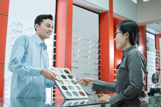 Een mannelijke winkelbediende houdt een monster van lenzenvloeistof lenzen vast en een klant wijst met zijn vinger om lenzenvloeistof lenzen te selecteren in de brillenwinkel