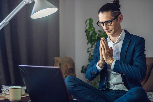 Een mannelijke zakenman mediteert in de lotuspositie terwijl hij thuis hard werkt met behulp van een laptop