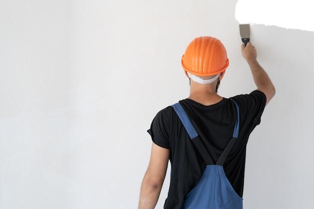 Een mannenbouwer is gekleed in speciale kleding en een oranje helm staat bij een witte muur. de muur plamuren. spatel in de hand. het werkproces. ruimte kopiëren