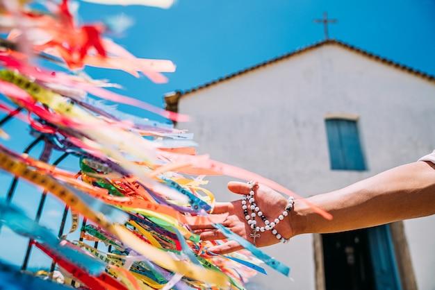 Een mannenhand die een bestelling plaatst met braziliaanse banden op het hek van een kerk in arraial d'ajuda, bahia, brazilië