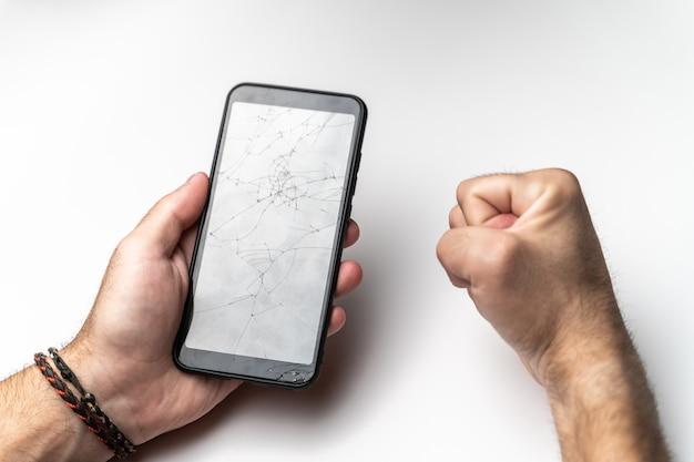 Een mannenhand en een gebalde vuist met een mobiele telefoon met een gebroken scherm.