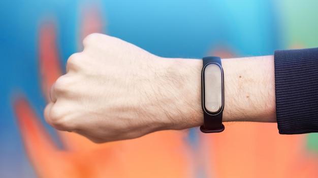 Een mannenhand gebalde in een vuist met fitness armband erop, veelkleurige achtergrond