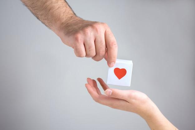 Een mannenhand geeft aan een vrouwelijke hand een witte doos met een hart, simbol van liefde, close-up.