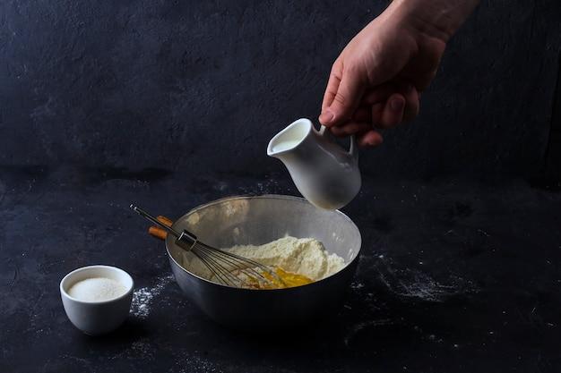 Een mannenhand giet melk van een melkboer in een metalen kom om deeg te maken. ingrediënten en gebruiksvoorwerpen voor het koken van cake op donkere tafel. het concept van het maken van deeg voor het bakken