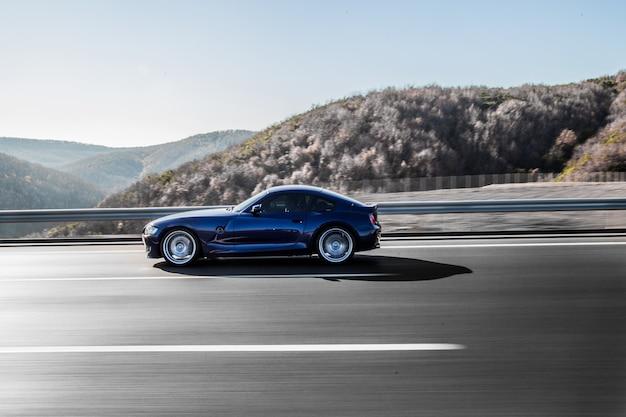 Een marineblauwe coupésedan die op de snelweg dwars door bergen rijdt.