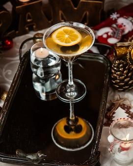 Een martini-glas alcoholische drank met zwarte olijven en citroenplak