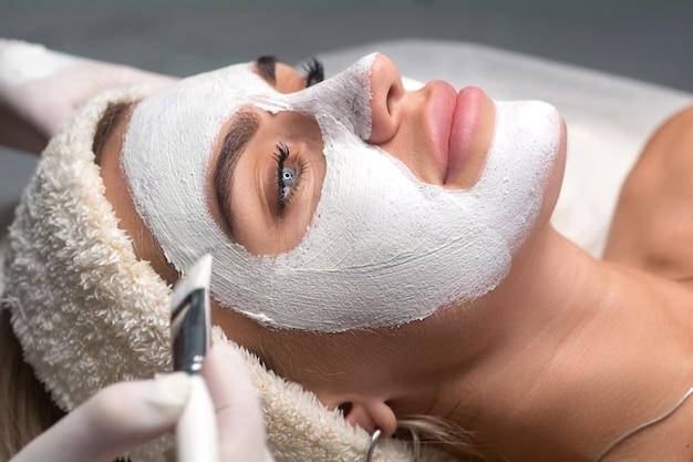 Een masker op het gezicht aanbrengen in een schoonheidssalon. schoonheidsspecialist en procedure voor verjonging