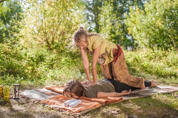 Een massageprofessional demonstreert verfrissende massagemethoden op het gras in het bos.