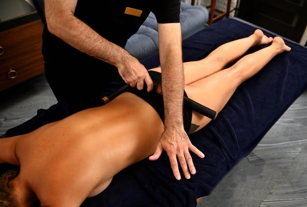Een massagetherapeut maakt een lichaamsmassage voor een jonge vrouw met behulp van een bamboestok. ayurvedische lichaamsverzorging in de spa