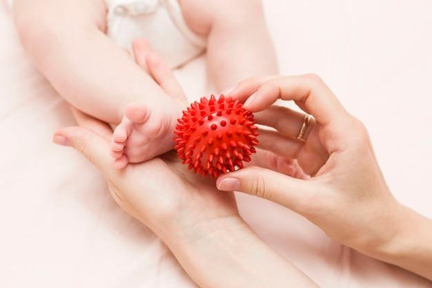 Een masseur, een moeder masseert de benen van de baby met een speciale bal - een igleball. kindermassage. selectieve aandacht.