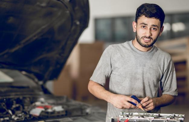 Een medebankman die de details van een auto repareert en olie toevoegt