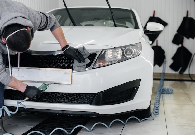 Een medewerker blaast en veegt de auto af na het wassen. carwash.