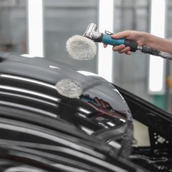 Een medewerker poetst het geverfde oppervlak van de auto