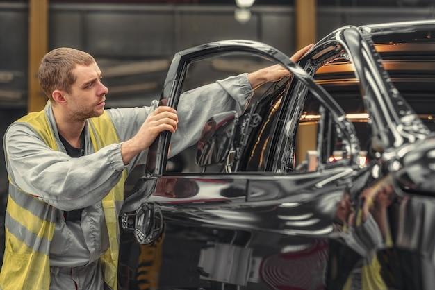 Een medewerker van de carrosserie-lakwinkel controleert de kwaliteit