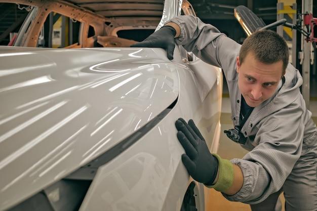 Een medewerker van de kwaliteitsafdeling van de autofabriek controleert de kwaliteit van de carrosserielak.