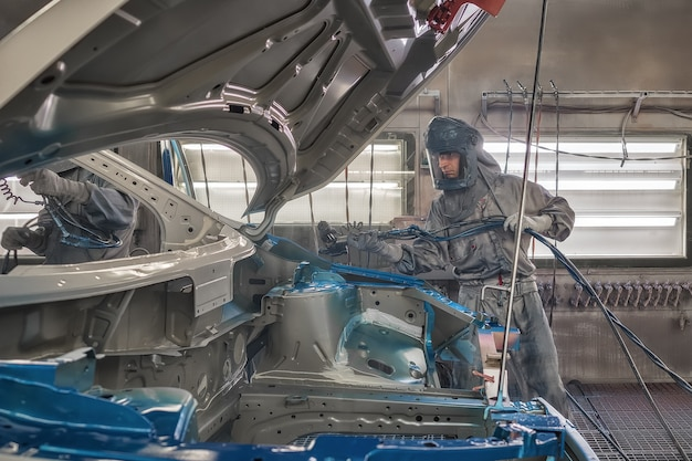 Een medewerker van de spuiterij van de autofabriek verft auto-onderdelen.