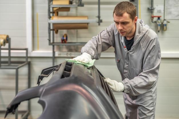 Een medewerker van de spuiterij van de autofabriek verwijdert stof met een wasdoek en bereidt de bumpers voor op het lakken