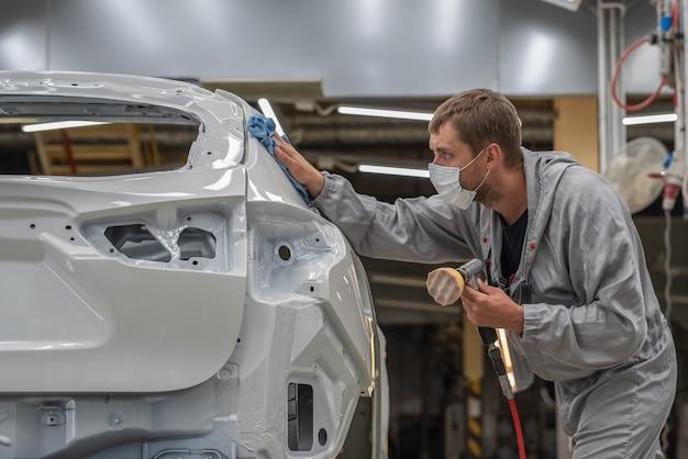 Een medewerker van de spuiterij van een autofabriek poetst het geverfde oppervlak