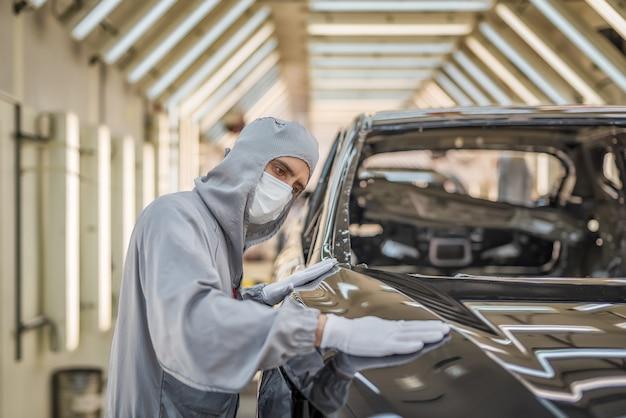 Een medewerker van de spuiterij van een autofabriek