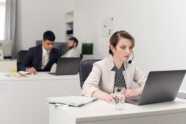 Een medewerker van een callcenter zit aan een balie in het kantoor van een groot financieel bedrijf in een strikte dresscode voor het kantoor.