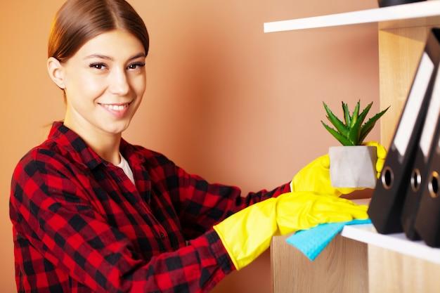 Een medewerker van een schoonmaakbedrijf veegt het stof van de planten