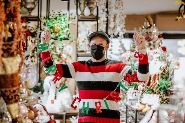Een medisch manisch masker houdt een slinger vast met letters en woorden merry christmas