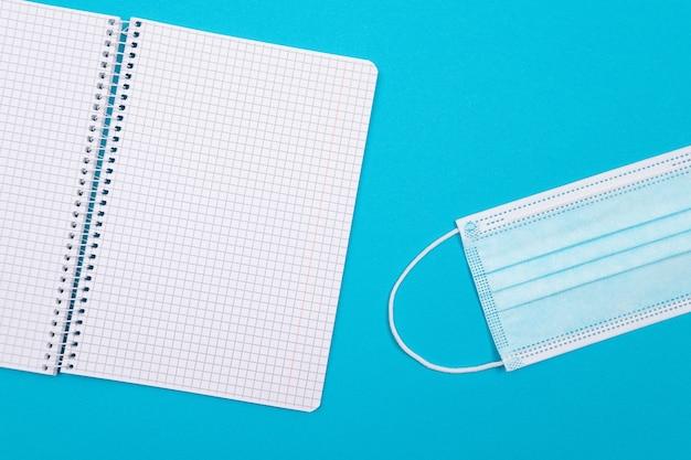 Een medisch masker en een notitieblok liggend op blauwe tafel