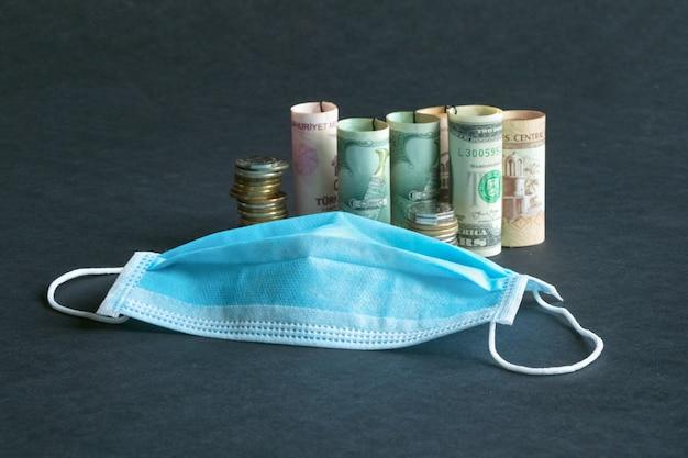 Een medisch masker en geld. pandemie en de economische crisis van het concept