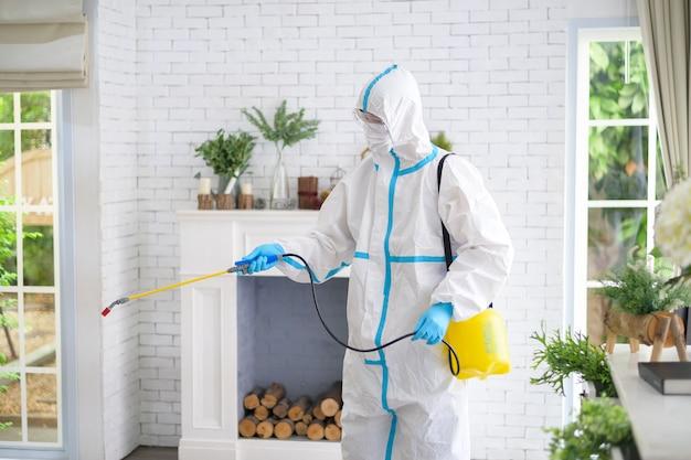 Een medisch personeel in pbm-pak gebruikt desinfecterende spray in de woonkamer, covid-19-bescherming, desinfectieconcept.