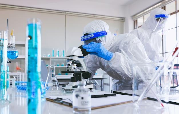 Een medische professional in een antiplaguepak is volledig beschermd tegen het virus en draagt steriele rubberen handschoenen en kijkt door de lens van een microscoop terwijl hij in een laboratorium zit.