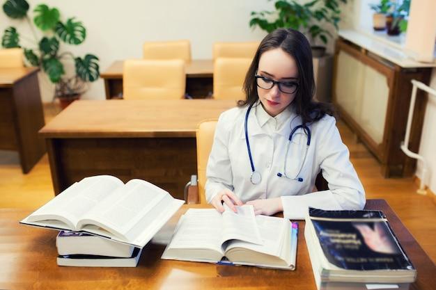 Een medische student voor studieboeken. de studie van chirurgie door een mooi meisje in de bibliotheek. verpleegster