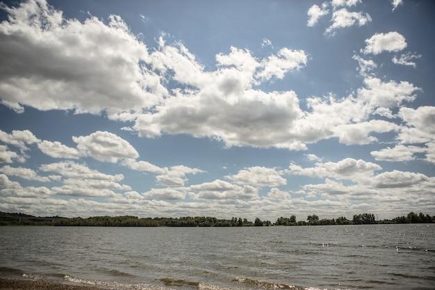 Een meer onder de bewolkte hemel met een bos
