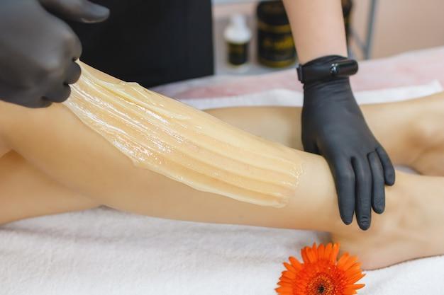 Een meester brengt een shugaring-pasta aan op het been van een jonge vrouw om haar te verwijderen sugaring ontharen