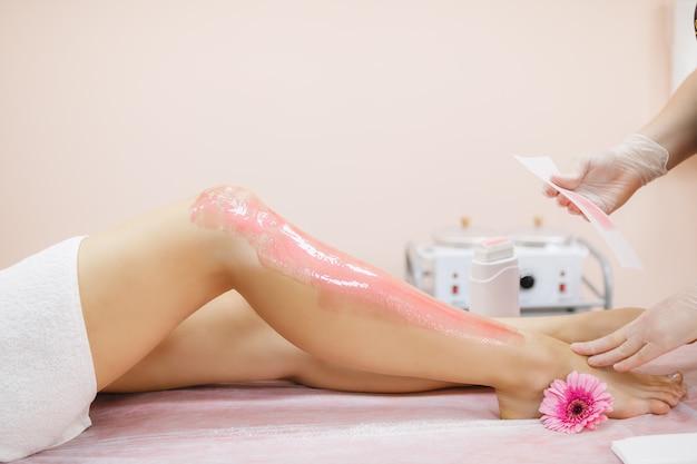 Een meester brengt roze ontharingswas aan op het been van een jonge vrouw om haar te verwijderen