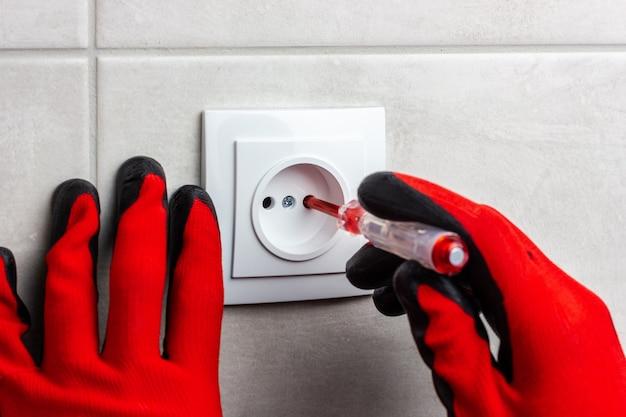 Een meester-elektricien controleert de spanning op het stopcontact met een indicatorschroevendraaier