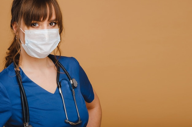 Een meisje arts staat in een medisch masker, geïsoleerd op een grijze achtergrond.