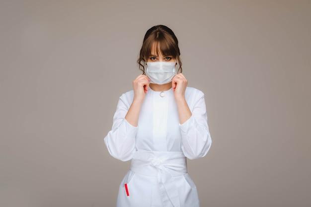 Een meisje arts staat in een medisch masker, geïsoleerd op grijs