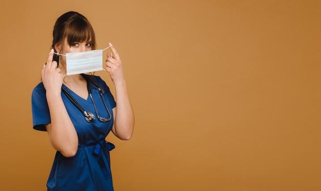 Een meisje arts staat in een medisch masker op een bruine muur