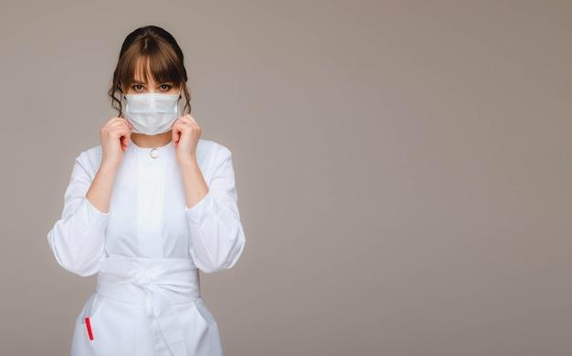 Een meisje arts staat in een medisch masker op een grijze muur