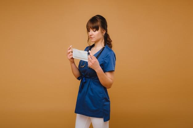Een meisje arts staat in een medisch masker